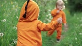 irmãos : Little twin boys in bright orange hoodies walk in nature, slow motion Vídeos