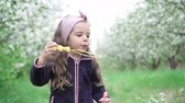 медленно : Little girl playing with soap bubbles in blooming garden, slow motion