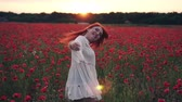 медленно : Red-haired woman throws her hair up standing in field of poppies in rays of setting sun, rear view