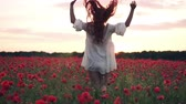 coquelicot : Joyful red-haired woman jumps up in flowered poppy field at sunset, slow motion Vidéos Libres De Droits