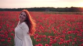 bieg : Joyful red-haired woman runs through flowering field of poppies and turns around towards camera.