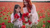 ポピー : Mom teaches little daughter to weave wreath of flowers in flowering poppy field at sunset