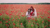 медленно : Mom teaches little daughter to weave wreath of flowers in flowering poppy field at sunset, overall plan