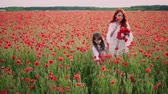 медленно : Young mother and little daughter collect wild poppy flowers to weave wreaths, slow motion