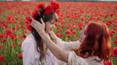 медленно : Young mother puts wreath of poppy flowers on her daughters head, slow motion