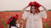 медленно : Young mother puts on her head crown of wild poppies in presence of his little daughter, slow motion