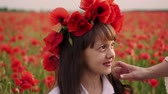 медленно : Close-up face of little girl with wreath of red poppy flowers on her head