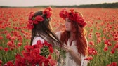 coquelicot : Young mother puts wreath of poppy flowers on her daughters head, slow motion