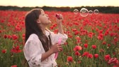 kolaylık : Little girl blowing soap bubbles in blooming field of red poppies at sunset, slow motion