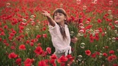 kolaylık : Little smiling girl catches soap bubbles in blooming field of red poppies, slow motion