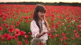 snadnost : Little smiling girl catches soap bubbles in blooming field of red poppies, slow motion