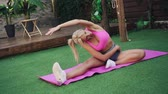 позы : Young athletic woman performs stretching exercise on green lawn, slow motion, concept of healthy lifestyle Стоковые видеозаписи