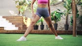 позы : Young athletic woman performs stretching exercise on green lawn, concept of healthy lifestyle