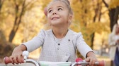 детский : Portrait of little smiling girl on bicycle in autumn afternoon Стоковые видеозаписи