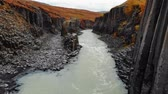 Drone fly back over canyon of black basalt columns, Iceland
