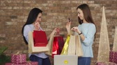 купить : Two girlfriends show each other their purchases, black Friday concept. Стоковые видеозаписи
