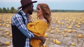Couple stands in pumpkin field and hugs, steadicam shot Stock Footage