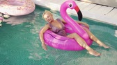 Young woman swims in a pool on an inflatable pink flamingo