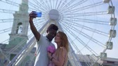 Young couple makes selfie on the background of a ferris wheel