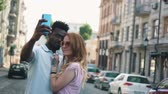 Young happy couple take selfie on a city street