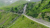 szerpentin : Aerial view of a waterfall over a road in the Carpathian mountains of Romania, a drone flies around Stock mozgókép