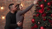 spouses : Young happy couple decorates xmas tree at home, man helps his girlfriend
