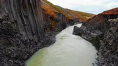 basalto : Drone flies over canyon of black basalt columns, Iceland