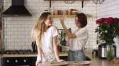 lesbian : Young happy couple of lesbians have fun dancing at home in the kitchen, valentines day concept.