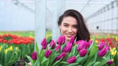 Young beautiful smiling woman greenhouse worker picks up a box with blooming tulips and walks towards the camera.