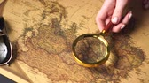 növelni : Woman traveler examines a map of the world with a magnifier, close up of hand. Slider shot. Stock mozgókép