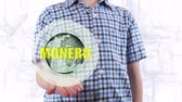 commerce : Young man shows a hologram of the planet Earth and text Monero. Boy with future technology 3d projection on a modern white digital background