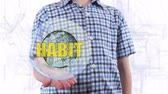 implemento : Young man shows a hologram of the planet Earth and text Habit. Boy with future technology 3d projection on a modern white digital background