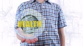 identify : Young man shows a hologram of the planet Earth and text Health. Boy with future technology 3d projection on a modern white digital background Stock Footage