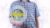 dividend : Young man shows a hologram of the planet Earth and text Money. Boy with future technology 3d projection on a modern white digital background Stock Footage