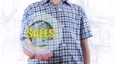 kısıtlı : Young man shows a hologram of the planet Earth and text Sales. Boy with future technology 3d projection on a modern white digital background Stok Video