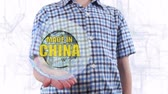 functioneel : Young man shows a hologram of the planet Earth and text Made in China. Boy with future technology 3d projection on a modern white digital background
