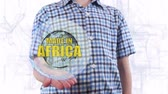 funzionale : Young man shows a hologram of the planet Earth and text Made in Africa. Boy with future technology 3d projection on a modern white digital background Filmati Stock