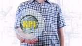 метрика : Young man shows a hologram of the planet Earth and text KPI. Boy with future technology 3d projection on a modern white digital background