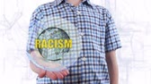 racism : Young man shows a hologram of the planet Earth and text Racism. Boy with future technology 3d projection on a modern white digital background Stock Footage