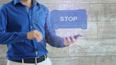 Man activates a conceptual HUD hologram with text Stop. The guy in the blue shirt and light trousers with a holographic screen on the background of the wall