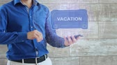 Man activates a conceptual HUD hologram with text Vacation. The guy in the blue shirt and light trousers with a holographic screen on the background of the wall