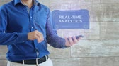 Man activates a conceptual HUD hologram with text Real-time analytics. The guy in the blue shirt and light trousers with a holographic screen on the background of the wall Dostupné videozáznamy