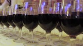 vino : The waiter pours wine into glasses at a party. On the table rows of glasses with red wine. Camera movement from left to right