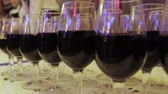 banquette : The waiter pours wine into glasses at a party. On the table rows of glasses with red wine. Camera movement from right to left