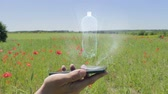 recyklace : Hologram of bottle on a smartphone. Person activates holographic image on the phone screen on the field with blooming poppies Dostupné videozáznamy