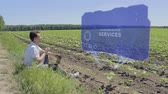 близость : Man is working on HUD holographic display with text Location-based services on the edge of the field. Businessman analyzes the situation on his plantation. Scientist examines future technology