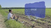 jutalom : Man is working on HUD holographic display with text Open on the edge of the field. Businessman analyzes the situation on his plantation. Scientist examines future technology Stock mozgókép