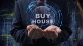 palabra : Male hands activate a conceptual holographic text Buy house. Businessman in a suit with a hologram of planet Earth on a background of a futuristic wireframe city Archivo de Video