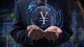 valuták : Male hands activate a conceptual holographic text Sign JPY. Businessman in a suit with a hologram of planet Earth on a background of a futuristic wireframe city Stock mozgókép