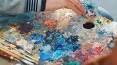 paleta : Artist mixes paints on the palette before painting a picture